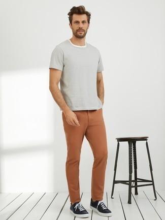 Outfits hombres: Elige una camiseta con cuello circular de rayas horizontales blanca y un pantalón chino en tabaco para conseguir una apariencia relajada pero elegante. Tenis de cuero negros son una opción perfecta para completar este atuendo.