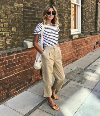 Elige por la comodidad con una camiseta con cuello circular de rayas horizontales en blanco y azul marino y una falda pantalón beige. Este atuendo se complementa perfectamente con sandalias planas de cuero doradas.