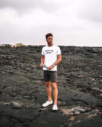 Cómo combinar: camiseta con cuello circular estampada en blanco y negro, pantalones cortos en gris oscuro, tenis de lona blancos, reloj de cuero marrón claro