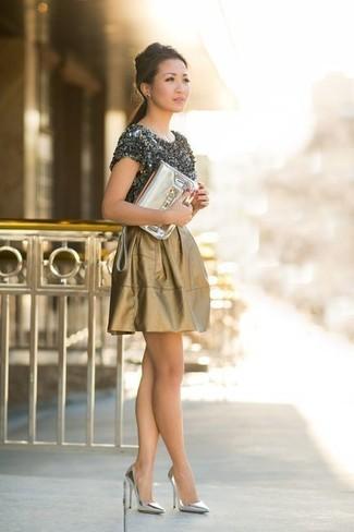 Cómo combinar: camiseta con cuello circular en gris oscuro, falda skater dorada, zapatos de tacón de cuero plateados, cartera sobre de cuero dorada