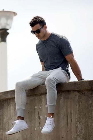 Cómo combinar: camiseta con cuello circular en gris oscuro, pantalón de chándal gris, zapatillas altas de cuero blancas, gafas de sol negras