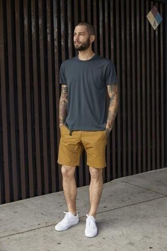 Outfits hombres en clima caliente: Empareja una camiseta con cuello circular en gris oscuro junto a unos pantalones cortos mostaza para una vestimenta cómoda que queda muy bien junta. Tenis de lona blancos son una opción práctica para complementar tu atuendo.