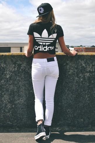Cómo combinar: camiseta con cuello circular estampada en negro y blanco, vaqueros pitillo blancos, zapatillas altas en negro y blanco, gorra inglesa estampada en negro y blanco