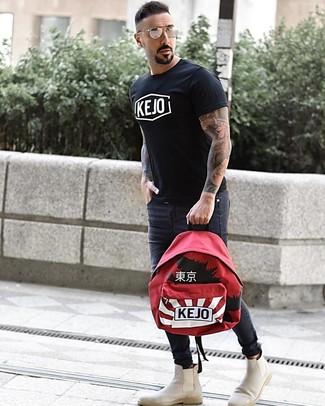 Look de moda: Camiseta con cuello circular estampada en negro y blanco, Vaqueros pitillo en gris oscuro, Botines chelsea de ante en beige, Mochila estampada roja