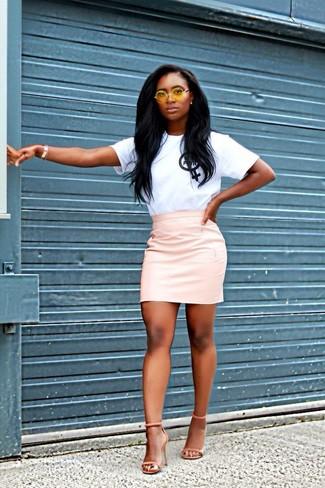 Una camiseta con cuello circular estampada en blanco y negro y una minifalda de cuero rosada son tu atuendo para salir los días de descanso. ¿Te sientes ingenioso? Dale el toque final a tu atuendo con sandalias de tacón de ante naranjas.