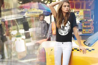 Look de Cara Delevingne: Camiseta con cuello circular estampada negra, Vaqueros pitillo blancos