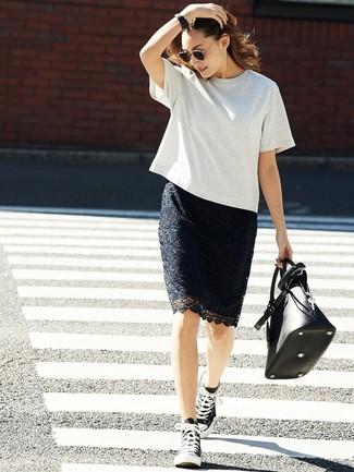 Cómo combinar: camiseta con cuello circular gris, falda lápiz de encaje negra, zapatillas altas de lona en negro y blanco, bolsa tote de cuero negra