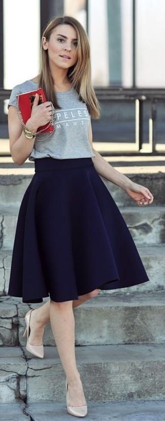Cómo combinar: camiseta con cuello circular estampada gris, falda skater azul marino, zapatos de tacón de cuero en beige, reloj dorado