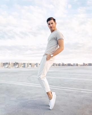 Cómo combinar: camiseta con cuello circular gris, pantalón chino blanco, tenis de lona blancos, reloj de cuero marrón claro