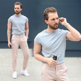 Cómo combinar: camiseta con cuello circular gris, pantalón chino rosado, tenis blancos