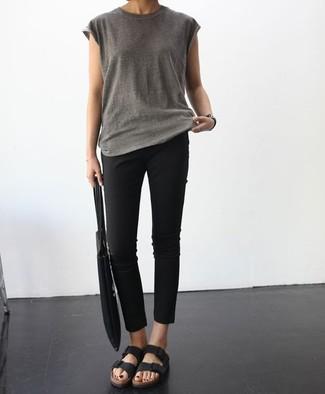 Cómo combinar: camiseta con cuello circular gris, pantalones pitillo negros, sandalias planas de cuero negras, bolsa tote de lona negra