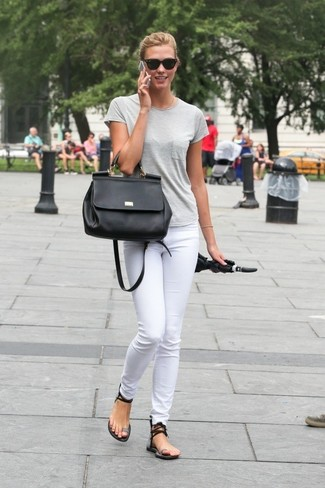 Cómo combinar: camiseta con cuello circular gris, vaqueros pitillo blancos, sandalias planas de cuero negras, bolso de hombre de cuero negro