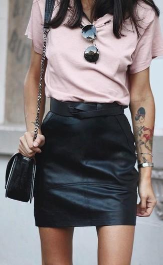 Cómo combinar una minifalda de cuero negra en clima caliente: Para un atuendo tan cómodo como tu sillón considera emparejar una camiseta con cuello circular rosada con una minifalda de cuero negra.