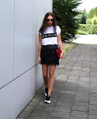 Cómo combinar: camiseta con cuello circular estampada en blanco y negro, minifalda de cuero сon flecos negra, deportivas en negro y blanco, cartera sobre de cuero burdeos