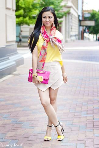 Una camiseta con cuello circular amarilla y una minifalda beige son tu atuendo para salir los días de descanso. Haz sandalias de tacón de cuero amarillas tu calzado para mostrar tu lado fashionista.