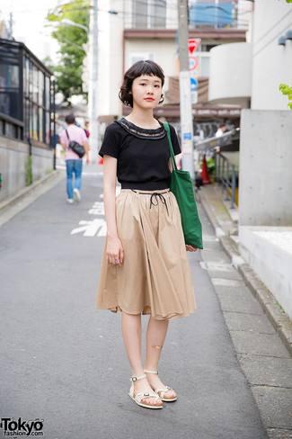 Cómo combinar: camiseta con cuello circular negra, falda midi plisada en beige, sandalias planas de cuero blancas, bolsa tote de lona verde