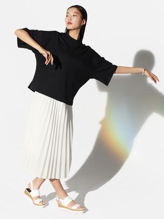 Cómo combinar: camiseta con cuello circular negra, falda midi plisada blanca, sandalias planas de cuero blancas