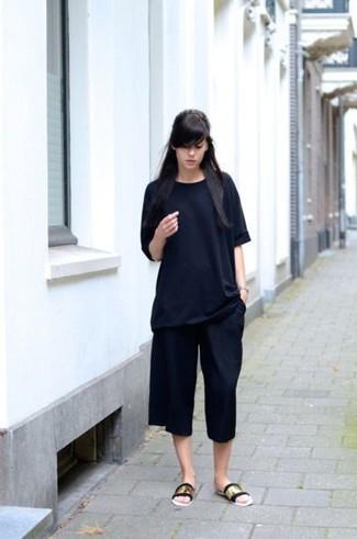 Considera ponerse una camiseta con cuello circular negra y una falda pantalón negra para un look agradable de fin de semana. ¿Quieres elegir un zapato informal? Elige un par de sandalias planas de cuero doradas para el día.