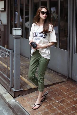 Cómo combinar: camiseta con cuello circular estampada en blanco y negro, pantalón capri verde oliva, sandalias de dedo en marrón oscuro, cartera sobre de cuero negra