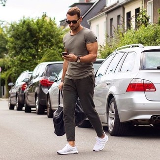 Cómo combinar: camiseta con cuello circular gris, pantalón chino en marrón oscuro, deportivas blancas, bolsa de viaje de cuero negra