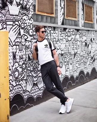 Cómo combinar: camiseta con cuello circular estampada en blanco y negro, pantalón chino en gris oscuro, deportivas blancas, mochila de cuero negra