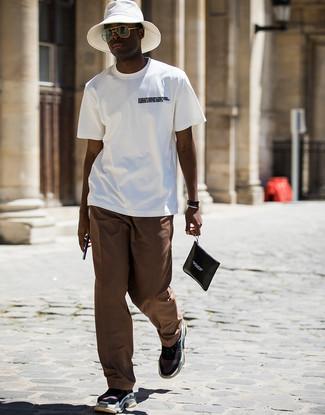 Cómo combinar: camiseta con cuello circular estampada en blanco y negro, pantalón chino marrón, deportivas negras, bolso con cremallera de cuero estampado en negro y blanco