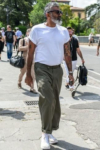 Outfits hombres: Ponte una camiseta con cuello circular blanca y un pantalón chino verde oliva para una vestimenta cómoda que queda muy bien junta. ¿Quieres elegir un zapato informal? Elige un par de deportivas blancas para el día.
