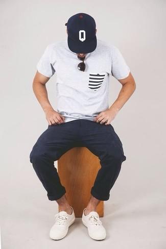 Cómo combinar: camiseta con cuello circular gris, pantalón chino azul marino, tenis blancos, gorra de béisbol estampada en azul marino y blanco