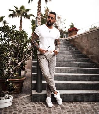 Cómo combinar: camiseta con cuello circular blanca, pantalón chino de rayas verticales en beige, tenis de cuero blancos, gafas de sol marrónes