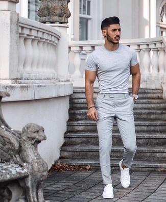 Cómo combinar un pantalón chino gris: Elige una camiseta con cuello circular gris y un pantalón chino gris para conseguir una apariencia relajada pero elegante. Tenis de lona blancos son una opción inigualable para complementar tu atuendo.