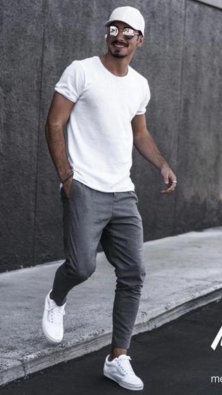 Cómo combinar: camiseta con cuello circular blanca, pantalón de chándal gris, tenis de lona blancos, gorra de béisbol negra