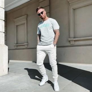 Look de moda: Camiseta con cuello circular estampada gris, Pantalón de chándal blanco, Tenis de cuero blancos, Gafas de sol negras