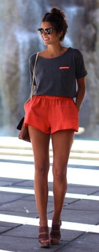 Cómo combinar: camiseta con cuello circular en gris oscuro, pantalones cortos rojos, sandalias con cuña de cuero marrónes, bolso bandolera de cuero marrón