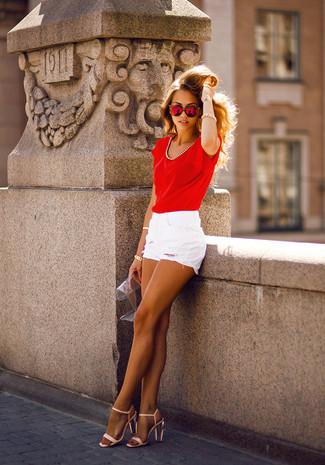 Emparejar una camiseta con cuello circular de seda roja y unos pantalones cortos es una opción cómoda para hacer diligencias en la ciudad. Con el calzado, sé más clásico y complementa tu atuendo con sandalias de tacón de cuero beige.
