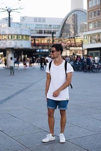 Cómo combinar: camiseta con cuello circular blanca, pantalones cortos vaqueros azules, tenis de cuero blancos, mochila de lona negra