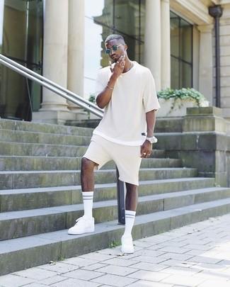 Cómo combinar: camiseta con cuello circular en beige, pantalones cortos en beige, tenis blancos, gafas de sol azul marino