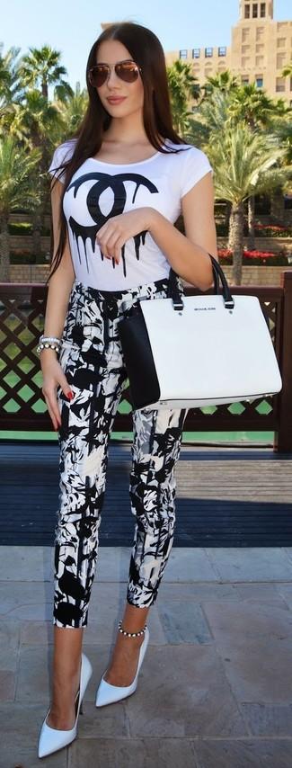 Cómo combinar: camiseta con cuello circular estampada en blanco y negro, pantalones pitillo estampados en blanco y negro, zapatos de tacón de cuero blancos, bolsa tote de cuero en blanco y negro
