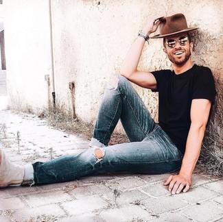 Cómo combinar: camiseta con cuello circular negra, vaqueros desgastados azul marino, botines chelsea de ante en beige, sombrero de lana marrón