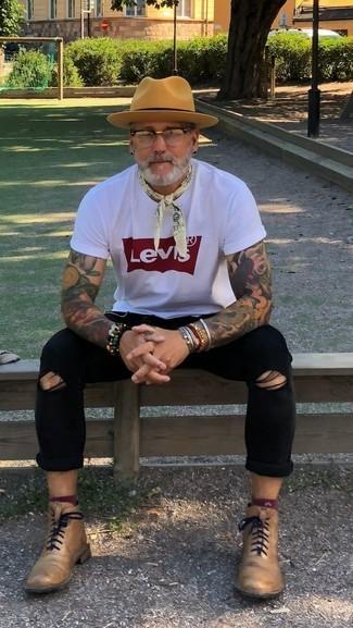 Cómo combinar: camiseta con cuello circular estampada en blanco y rojo, vaqueros pitillo desgastados negros, botas formales de cuero marrón claro, sombrero de lana marrón claro