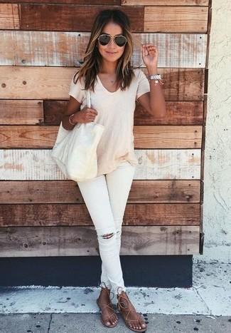 Cómo combinar: camiseta con cuello circular en beige, vaqueros pitillo desgastados blancos, sandalias de dedo de cuero marrónes, bolsa tote de cuero en beige