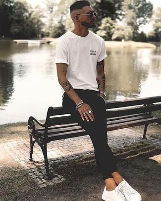 Outfits hombres estilo relajado: Intenta ponerse una camiseta con cuello circular estampada en blanco y negro y unos vaqueros pitillo negros transmitirán una vibra libre y relajada. ¿Te sientes valiente? Complementa tu atuendo con tenis de lona blancos.