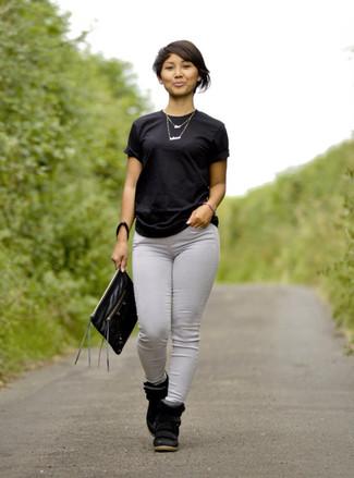 Cómo combinar: camiseta con cuello circular negra, vaqueros pitillo grises, zapatillas con cuña de ante negras, cartera sobre de cuero negra