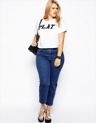 Cómo combinar: camiseta con cuello circular estampada en blanco y negro, vaqueros azules, sandalias de tacón de cuero gruesas plateadas, bolso bandolera de cuero negro