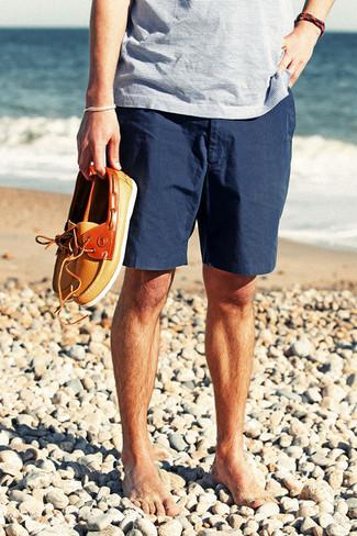 Una camiseta con cuello en v de rayas horizontales celeste y unos pantalones cortos azul marino son una opción inigualable para el fin de semana. Náuticos de cuero naranjas proporcionarán una estética clásica al conjunto.