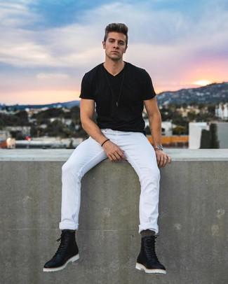 Cómo combinar: camiseta con cuello en v negra, vaqueros blancos, botas casual de cuero negras