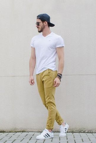Cómo combinar: camiseta con cuello en v blanca, pantalón chino mostaza, tenis de cuero blancos, gorra de béisbol negra
