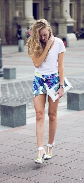 Cómo combinar: camiseta con cuello en v blanca, pantalones cortos con print de flores azules, sandalias de tacón de cuero blancas, cartera sobre de goma transparente