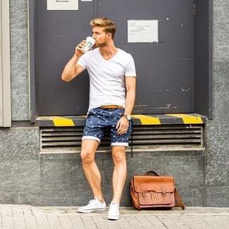 Cómo combinar: camiseta con cuello en v blanca, pantalones cortos estampados azul marino, tenis de lona blancos, bolso mensajero de cuero marrón claro