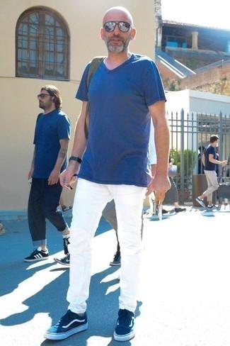Cómo combinar unos tenis de ante azules: Haz de una camiseta con cuello en v azul y unos vaqueros blancos tu atuendo para una apariencia fácil de vestir para todos los días. Tenis de ante azules son una opción perfecta para complementar tu atuendo.