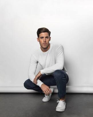 Cómo combinar: camiseta de manga larga blanca, pantalón chino azul marino, tenis de lona blancos